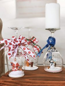 different figurines in wine glass snow globes