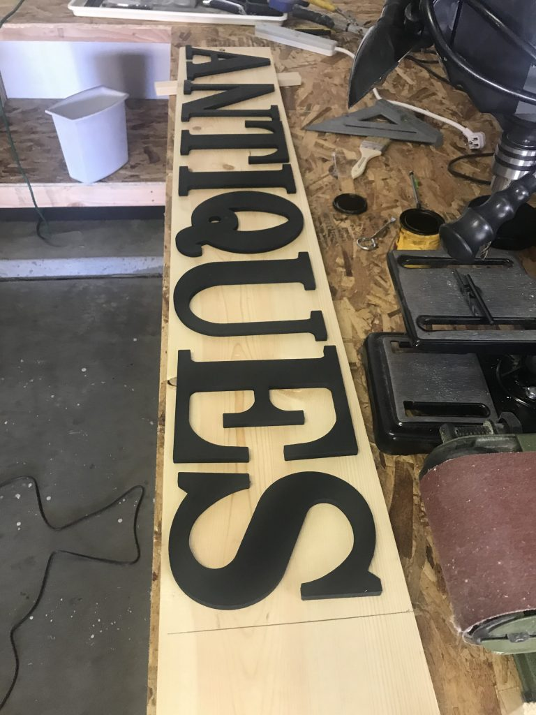Placing the wood letters on the Antiques Sign