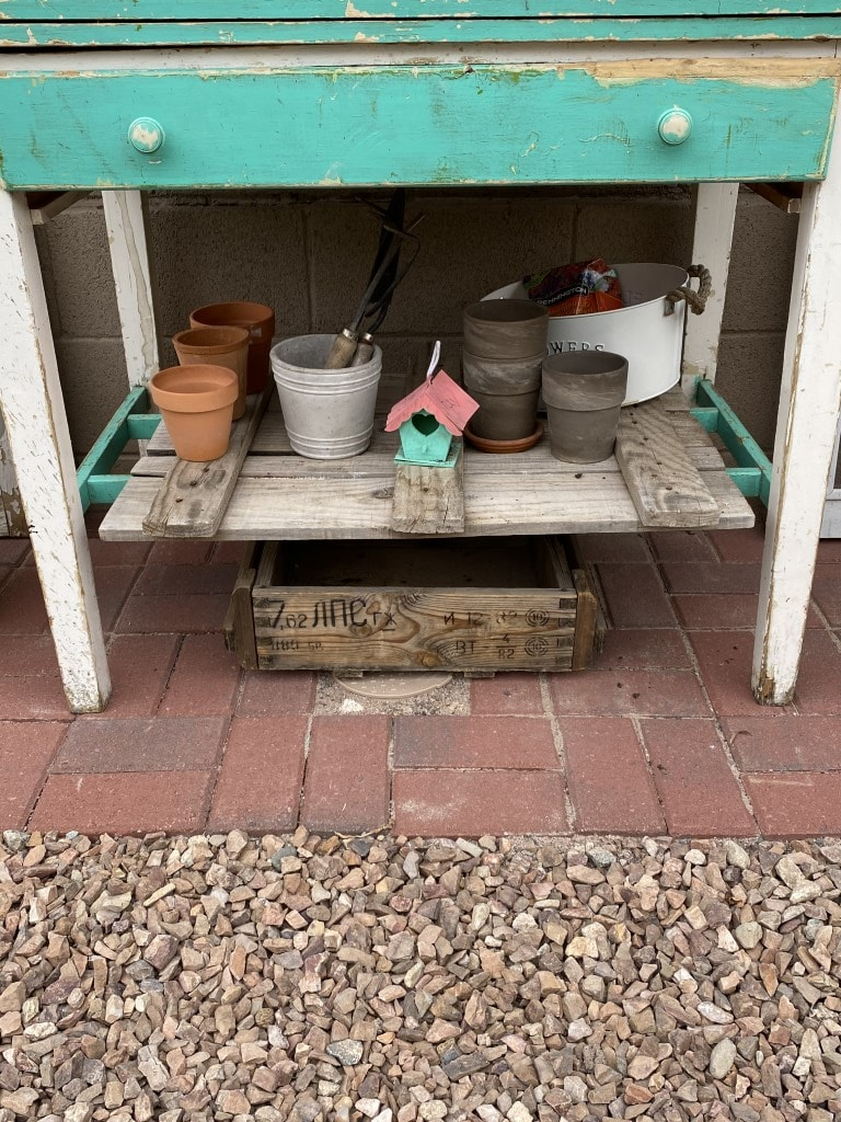 completed brick pad with potting bench sitting on it and valve box covred by an antique wood box.