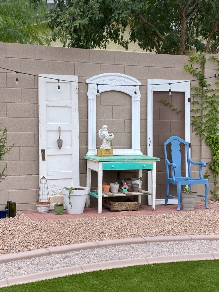 Potting bench sitting on brick pad with a chippy white door leaning agains the block wall on one side and a vintage screen door leaning agains the wall on the other side. there is an arched frame sitting on top of the table and leaning against the block wall!