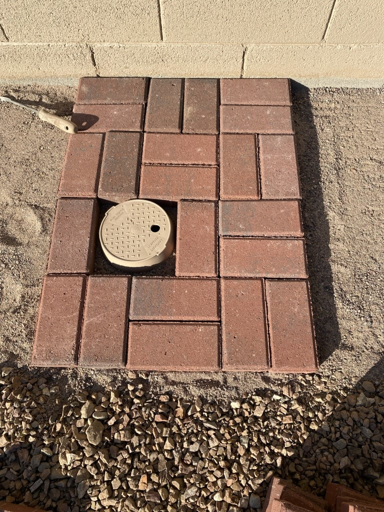 Irrigation valve box right in the middle of where brick is to be laid