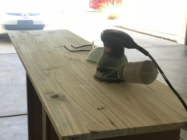 Sanding the wood for your industrial media console.