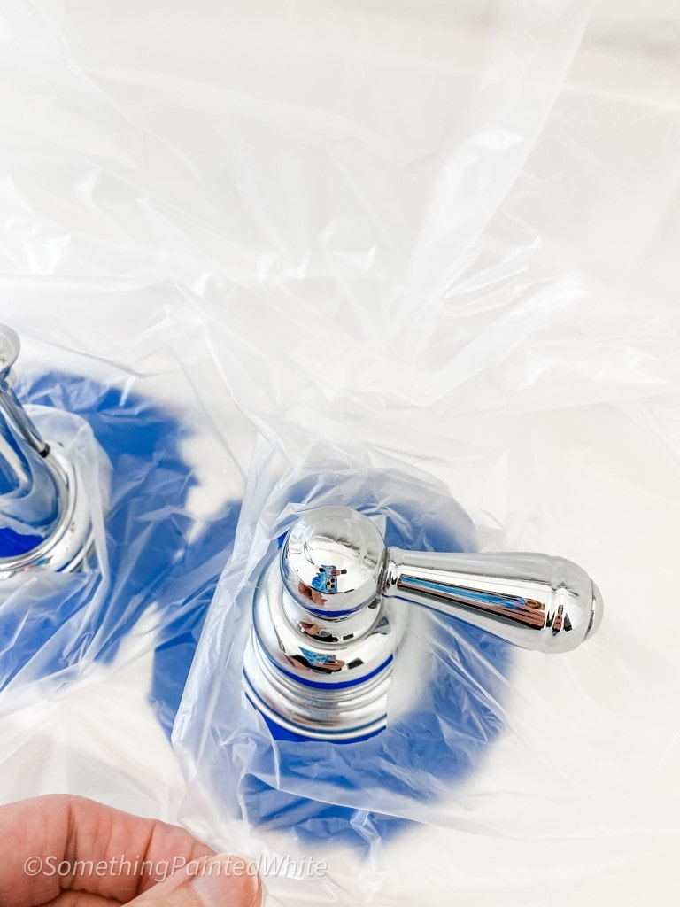 slipping the plastic over the faucet and handle in preparation for spray painting the bathroom faucets