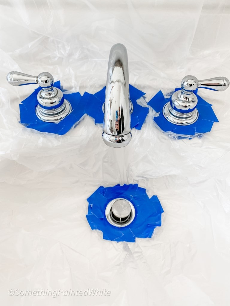 taped and plastic around faucet so only the faucet and handles are exposed for spray painting