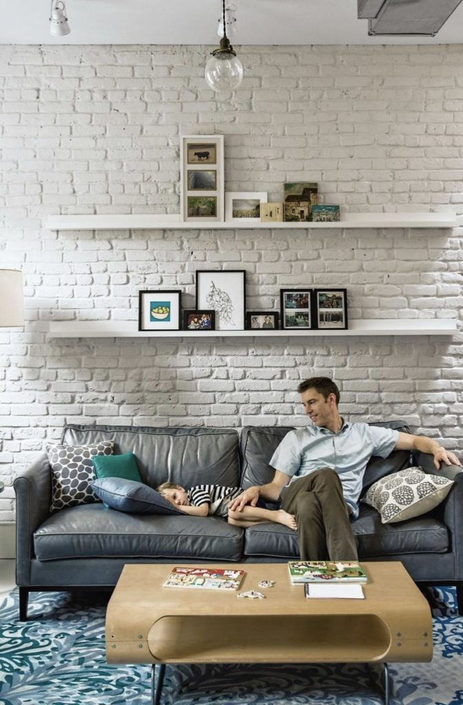 Photo of an old brick wall paited white, lots of texture and patching. With shelves on it and a sofa with dad and son sitting on it.
