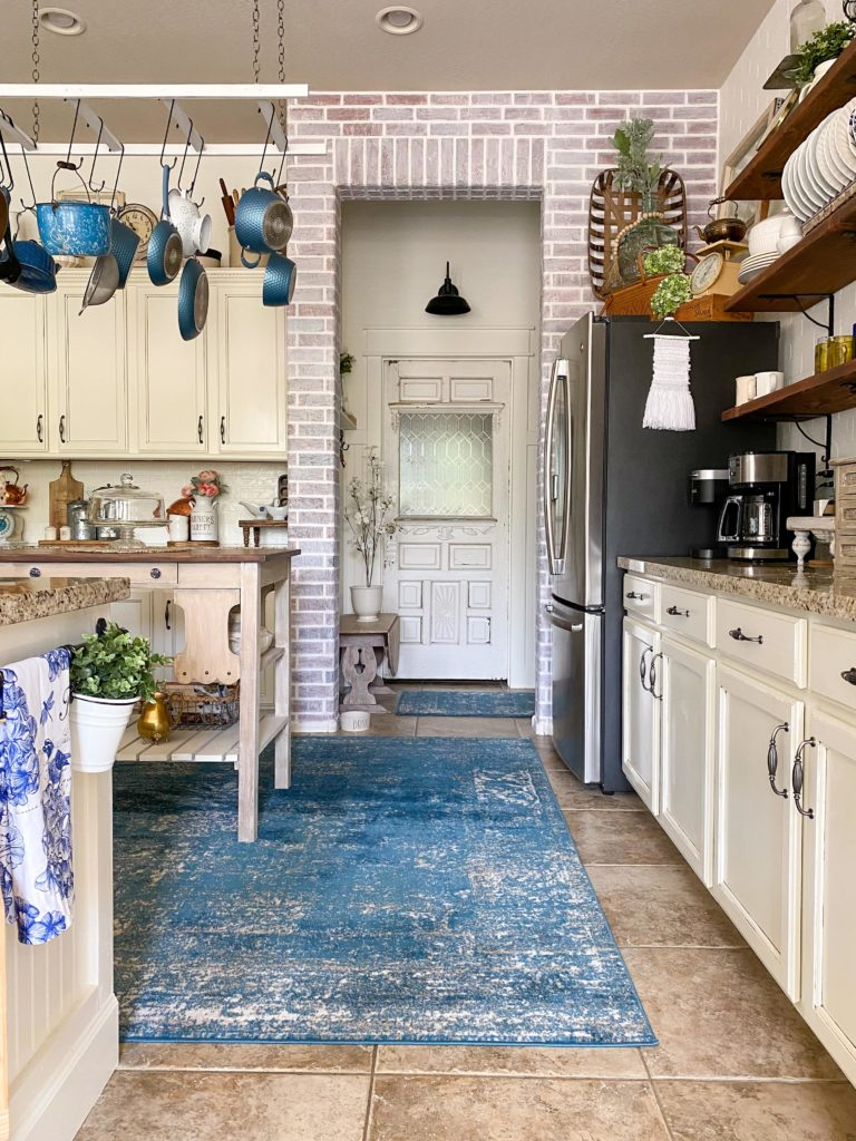View of kitchen looking toward brick accent wall with old farmhouse door in background and hanging pot rack to the left, open shelving over cabinets to the right, blue rug on floor under vintage libray desk made into island