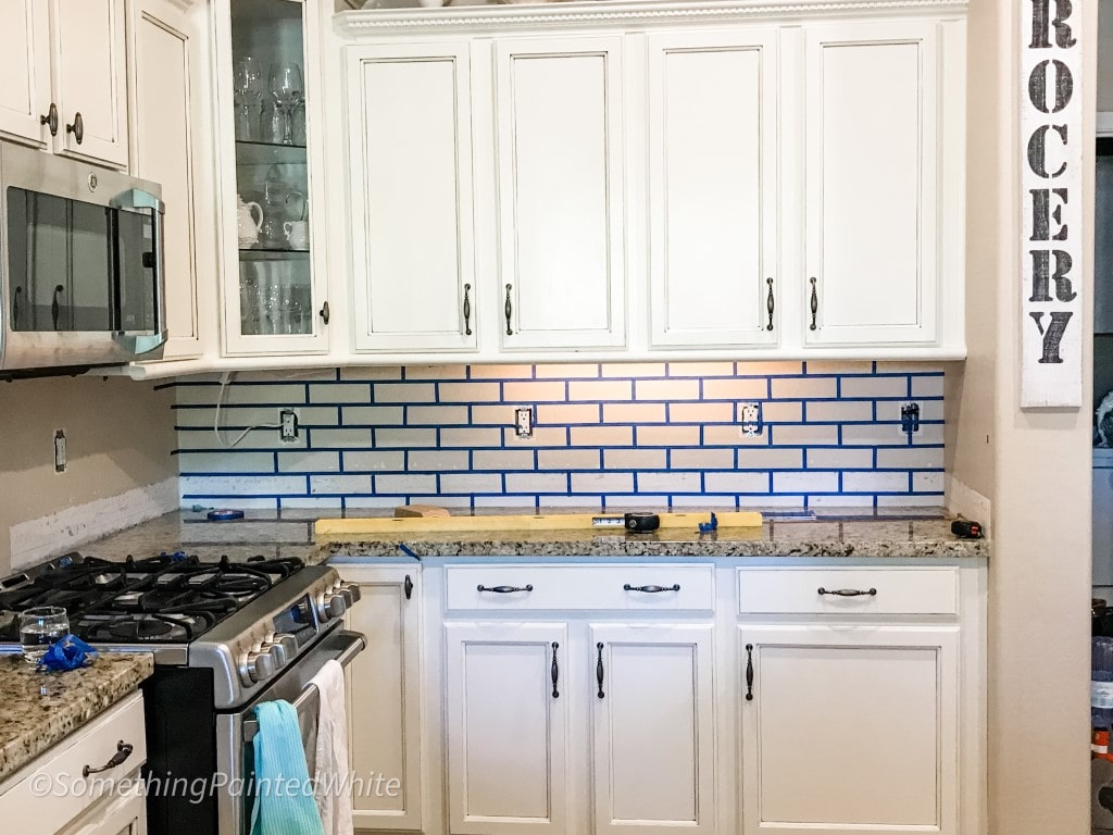 Brick pattern on wall with blue tape in preparation for faux brick wall using joint compound