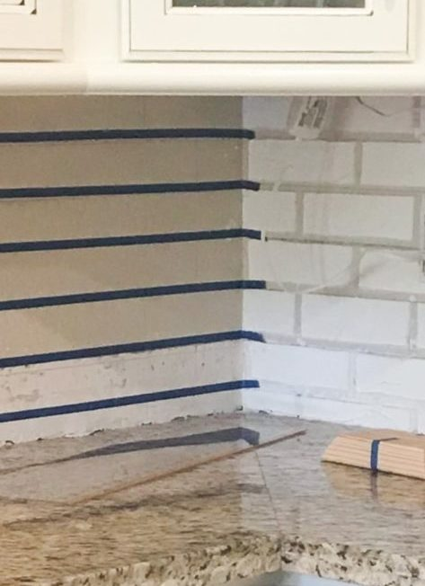 Close up showing how tape overlaps into grout lines of opposite wall in corner.