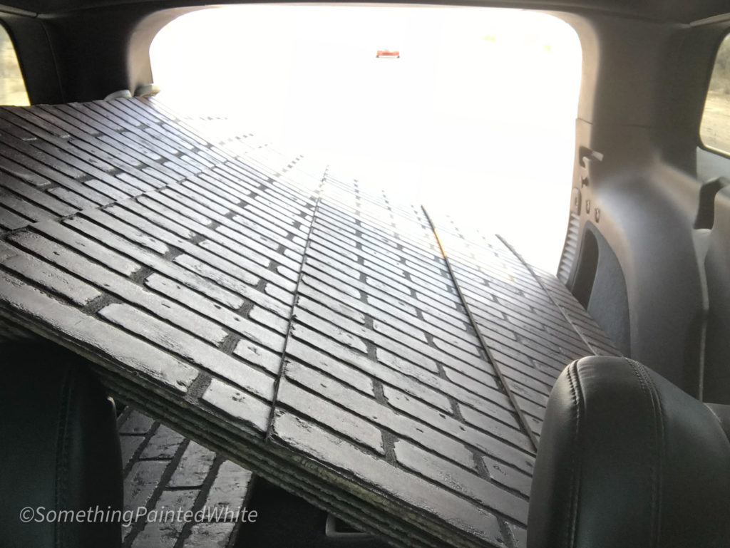 Brick panels loaded into the back of a Jeep for transport from store to home.