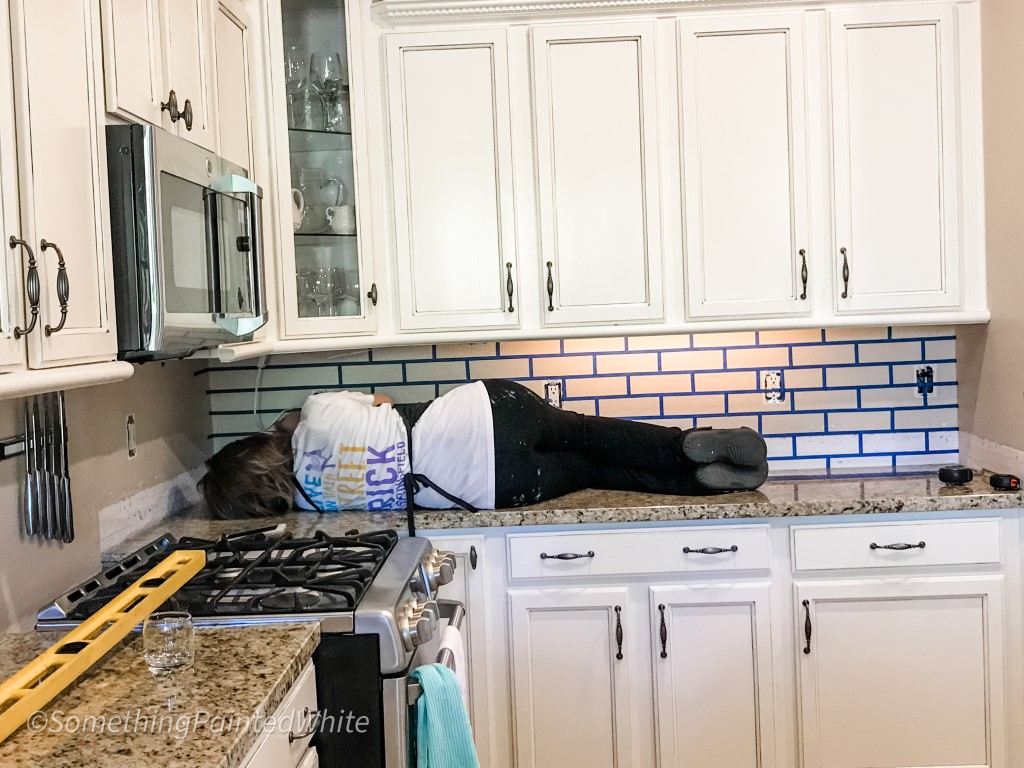 Laying on the counter taping brick pattern to the wall