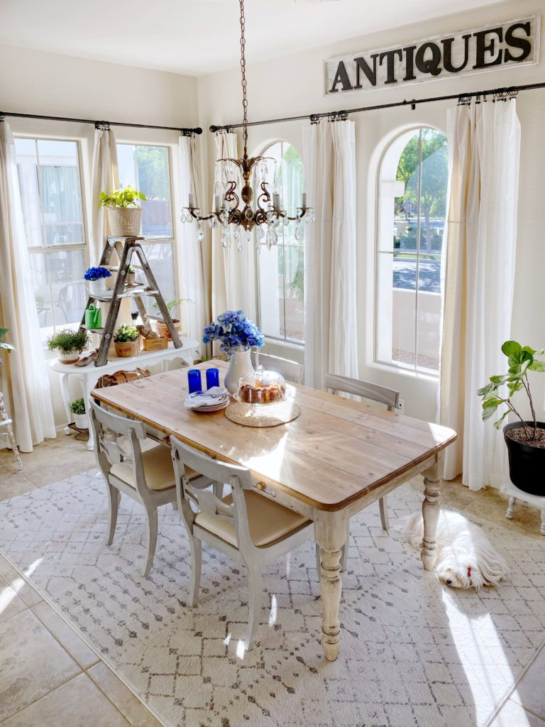 Dining room table with entry table sitting at end of room by a window with a ladder on top.