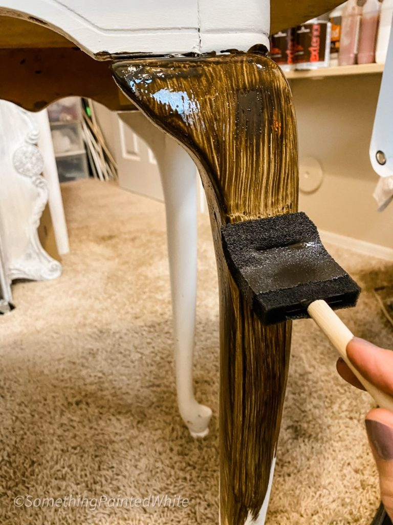 Brushing glaze on to the leg of the table with a sponge brush.