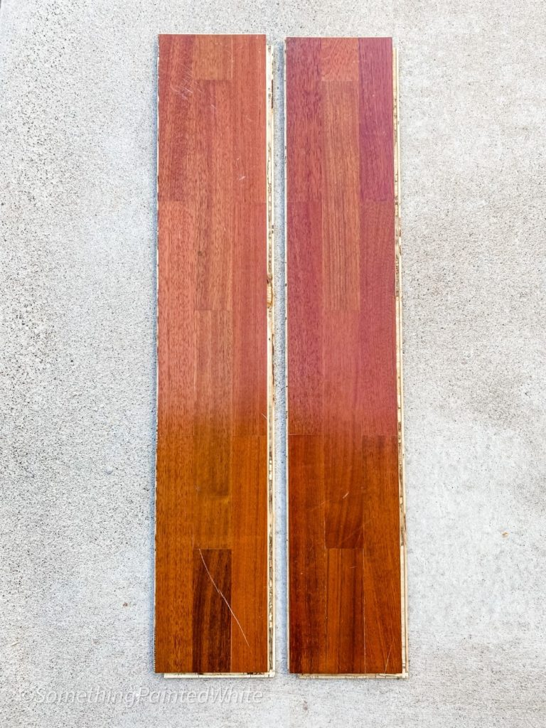 Two pieces of cherry stained wood flooring that will be used upside-down to create a shiplap feature wall.