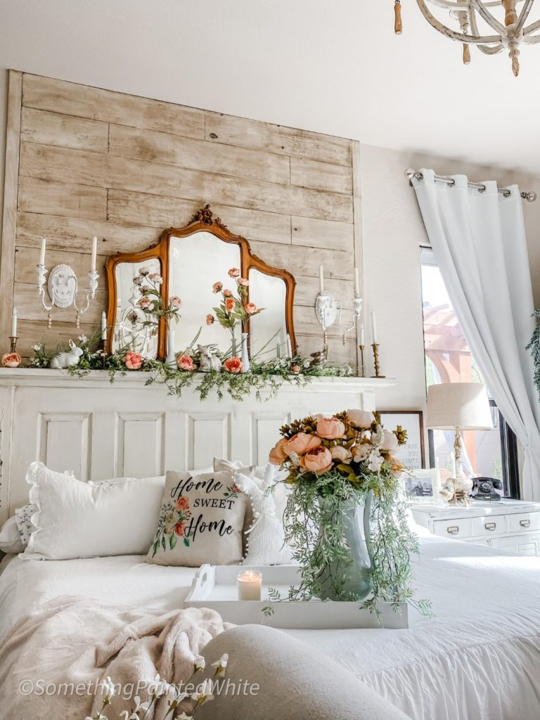 The finished wall with all the decor in place, including an antique mirror, candle sconces and spring flowers and greenery.