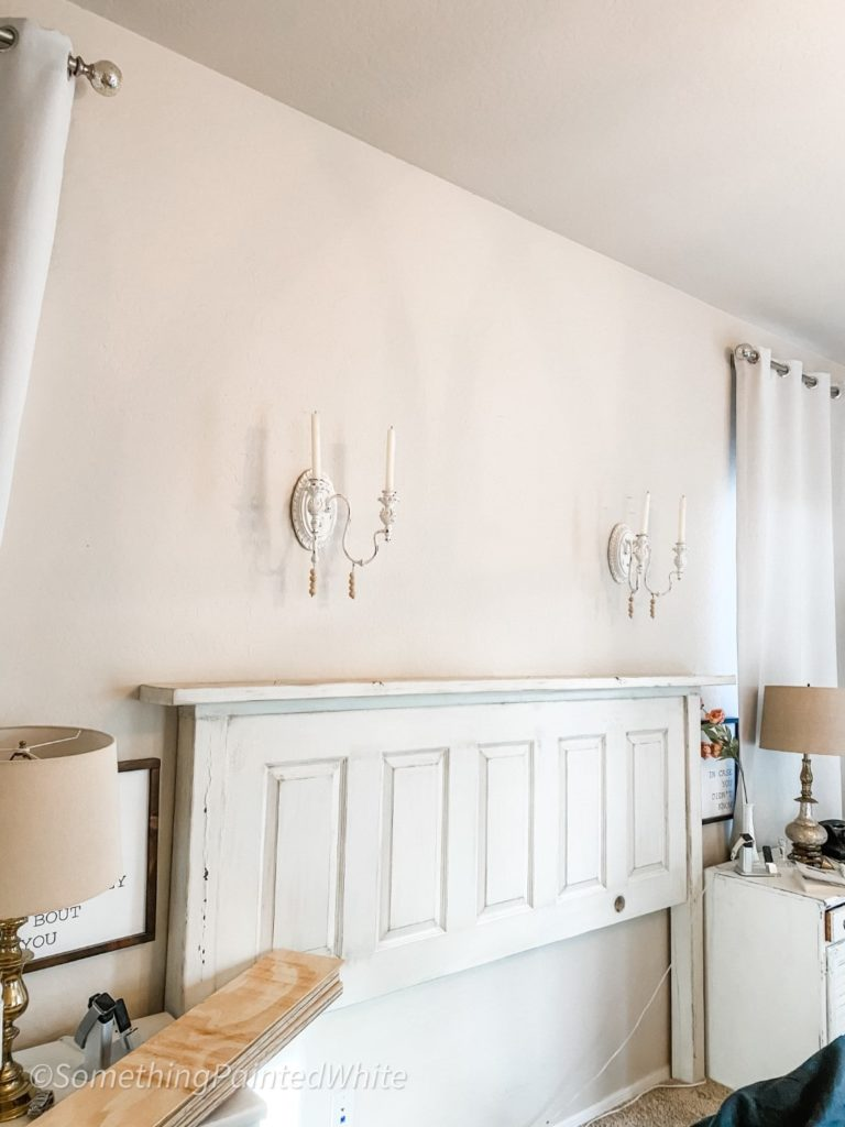 Wall above headboard with nothing except the candle sconces.