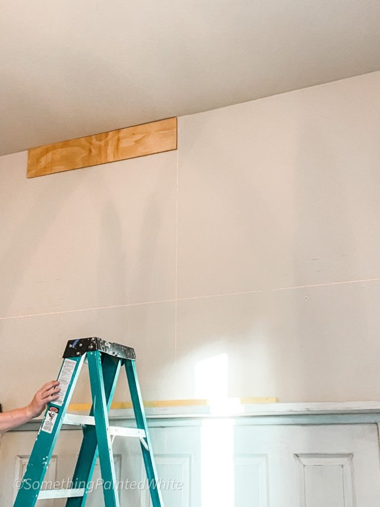 Using a laser level and starting the shiplap feature wall with the first board installed at the top of the wall!