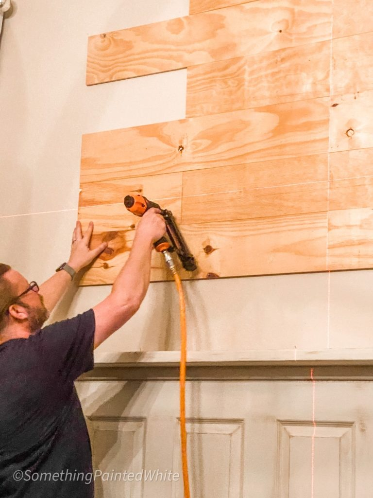 continuing to add upside-down floor boards to the wall as shiplap using a finish nailer.