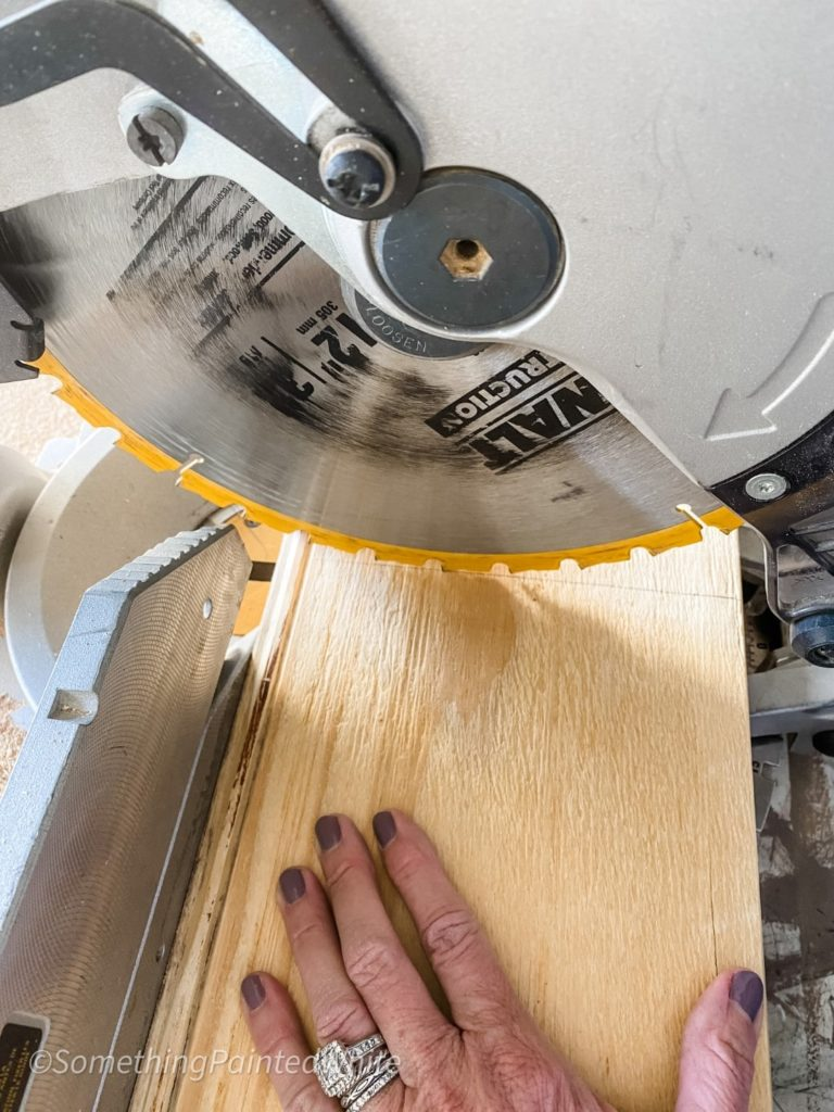 Using our miter saw to cut some pieces down to fit into our pattern.