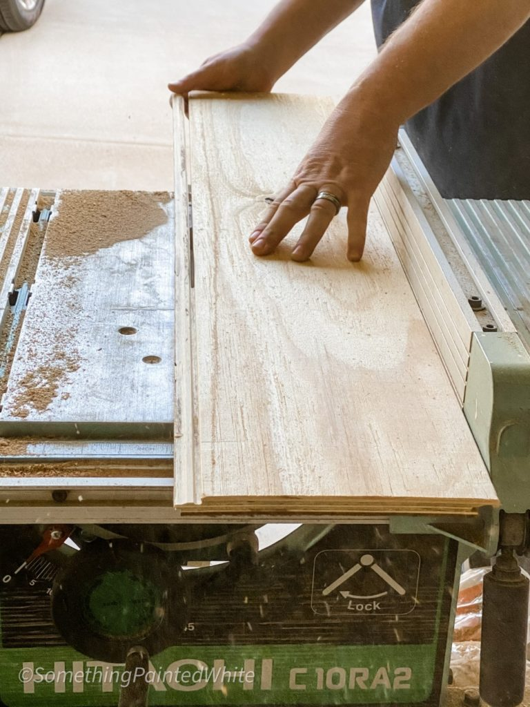 Running the wood through a table saw to remove the lip edge on one side and one end of each piece.
