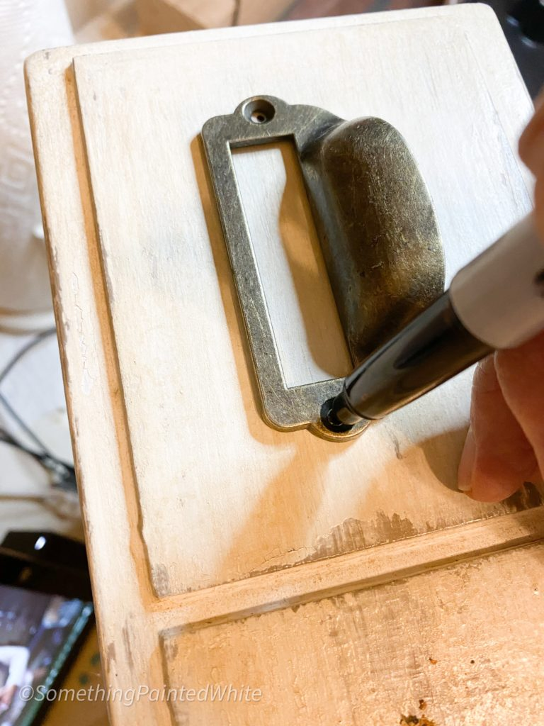 Marking where to drill pilot holes for the hardware on the drawer fronts.