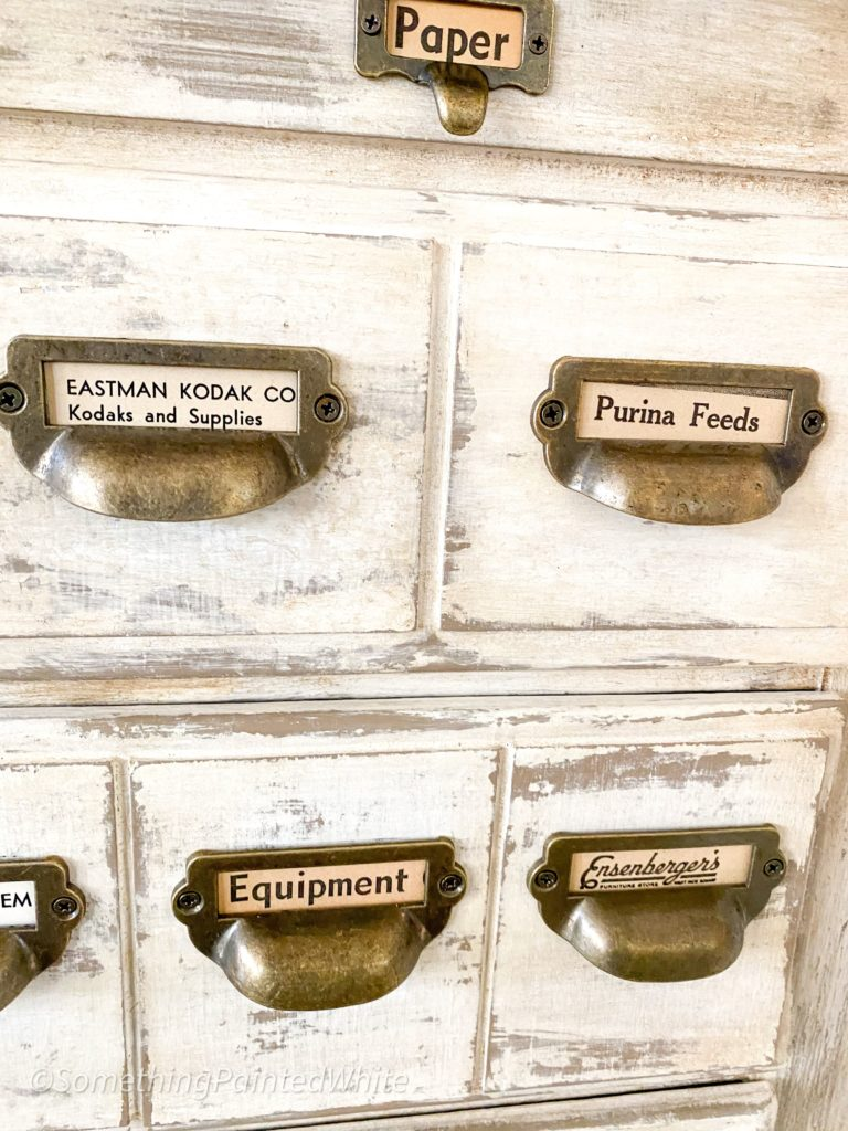 Completed apothecary chest with hardware and vintage newspaper clippings as labels.