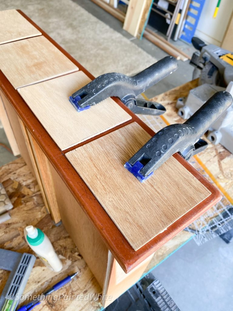 Clamping the false drawer fronts after they are glued on.