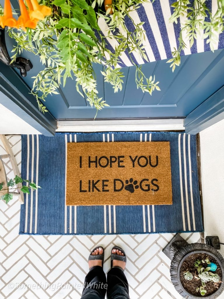 """Door mat that reads """"I hope you like dogs"""" with a blue outdoor rug under it, in front of the blue front door. looking down to show the greenery hanging on the front door, the mats, and my toes."""