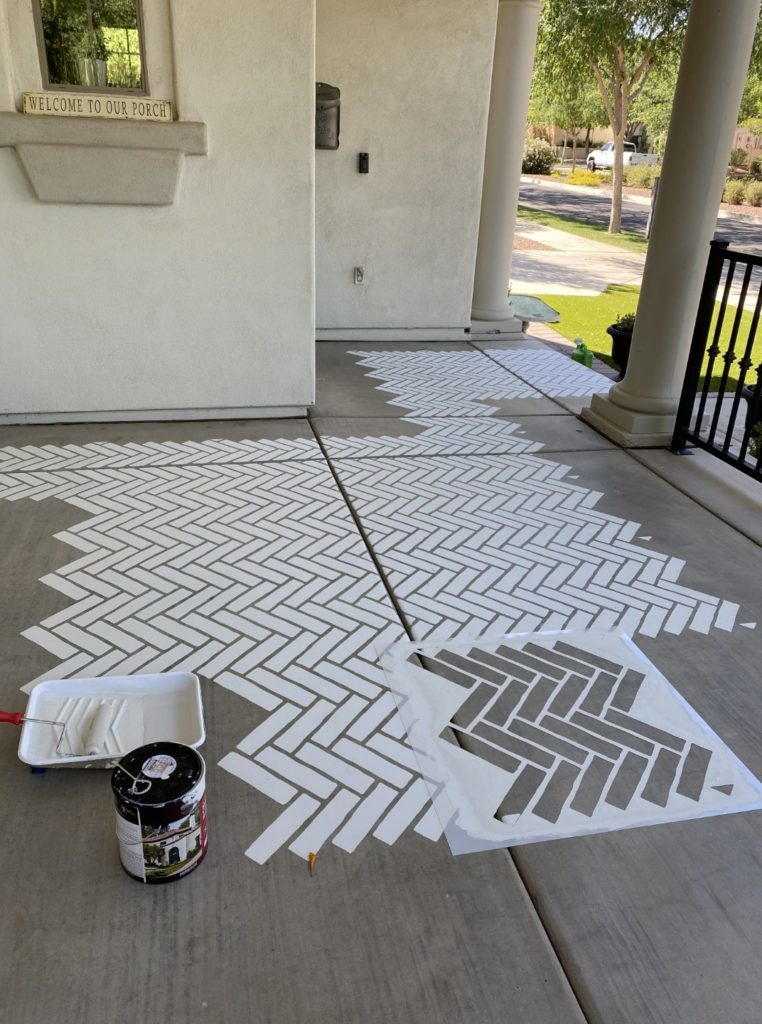Making progress with the stenciled porch. brick herringbone pattern painted white. about 1/3 done.