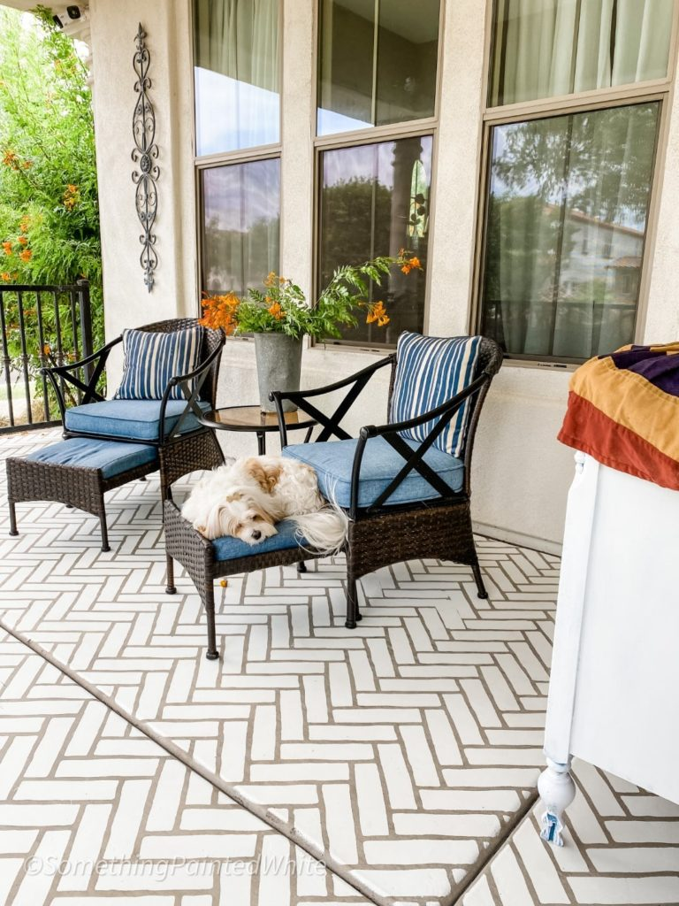 Showing the stenciled front porch after it is finished and decorated! Greta (the dog) is laying on the footstool of the patio furniture!
